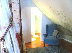 Room 6 with blue chair for relaxing and mural of tree on slanted wall