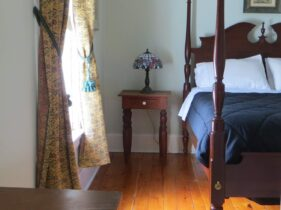 4-poster queen sized bed in Room 2 with tiffany lamp on nightstand