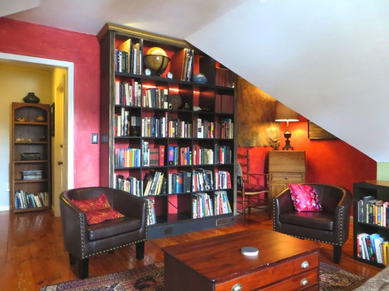 Library with red walls, books on shelves, chairs for reading