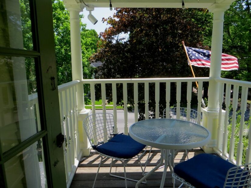 Tables and chairs on upstairs porch, with flag